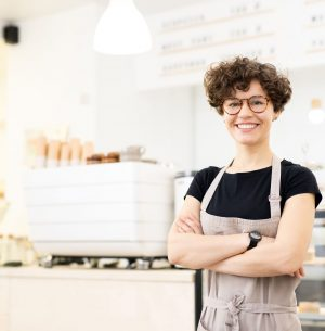 Smiling attractive hipster female barista standing in coffee shop and crossing arms on chest while looking at camera