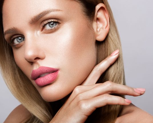 Beautiful young model with pink lips and nude manicure