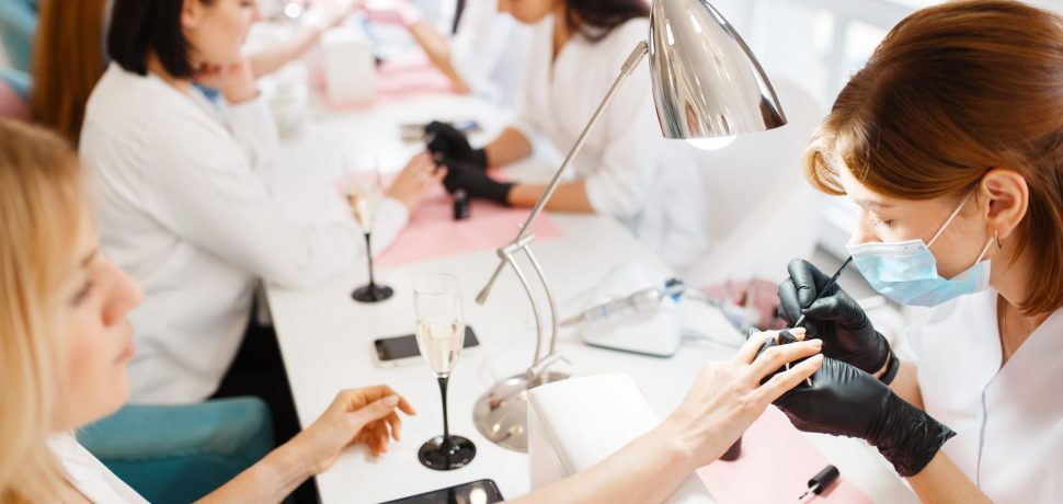 Group of women relax on manicure procedure in beauty salon. Professional beautician and female customers, nail care in spa studio, fingernail treatment