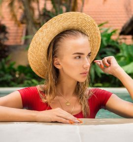 Close up portrait of a beautiful young woman in sexy red swimsuit and vintage straw hat in pool posing to camera. Hot sunny day. Tropic island vacation. Summer travel girl, active hipster lifestyle.