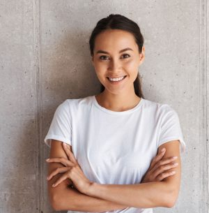 Smiling young asian woman standing with arms folded over gray wall background