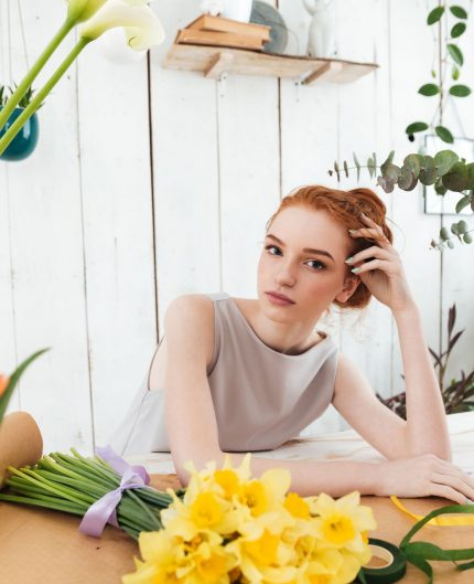 Tired young woman florist gazing at camera while working with different flowers in workshop