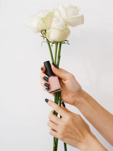Woman holds nail varnish and flowers, beauty salon, manicure and pedicure procedure. Professional beautician service, female customer, toenail and fingernail care in spa studio
