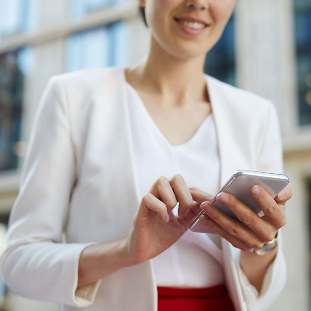 businesswoman-using-smartphone-outdoors-cropped-KAYU7S3