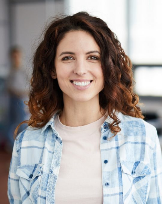 cheerful-young-woman-posing-in-creative-agency-P8NMKLX
