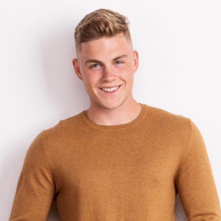 portrait-of-a-happy-young-man-standing-in-a-studio-QJW7ZN4
