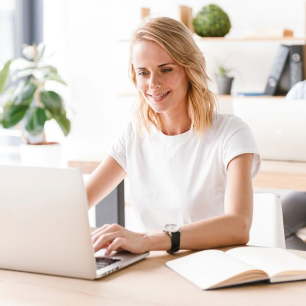 smiling-woman-manager-working-on-laptop-computer-G6KDQUS