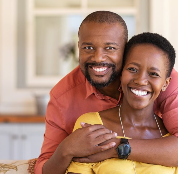 Happy mature black couple bonding to each other and smiling while sitting on couch. Portrait of smiling black man embrace his wife from behind and looking at camera. Smiling husband and beautiful woman laughing.