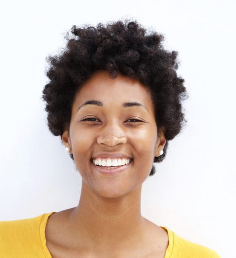 Closeup portrait of smiling young black woman against white background