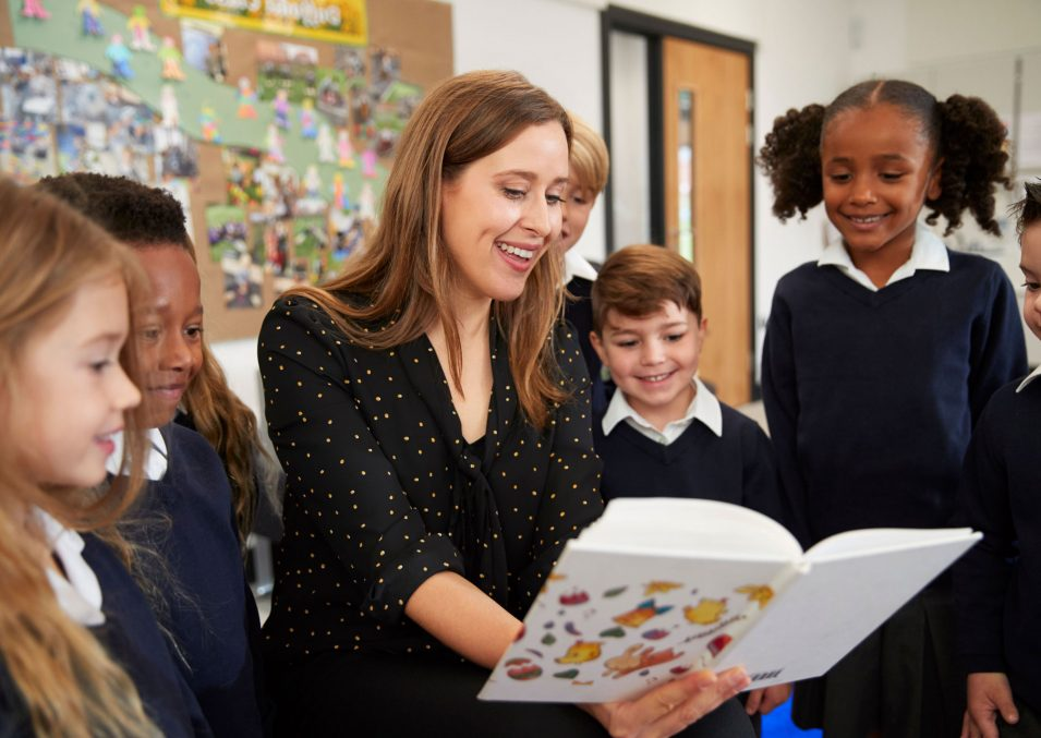 female-primary-school-teacher-reading-to-a-class-C65QJRL-rotate