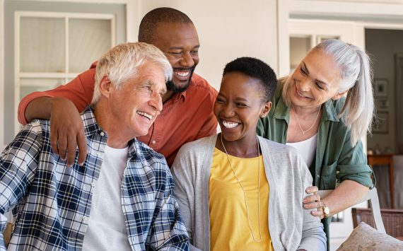 Cheerful friends sitting in courtyard enjoying the afternoon together. Group of four mature people sitting outside home and laughing. Happy senior man and old woman enjoying with mature african couple.