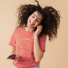 emotional-happy-excited-young-curly-woman-2JBV3GN