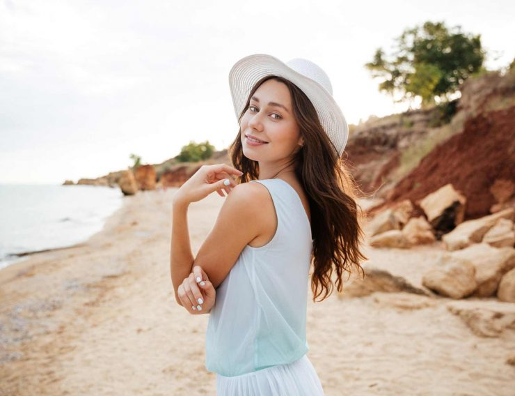 happy-young-woman-in-white-hat-waalking-near-the-PMPGEFG