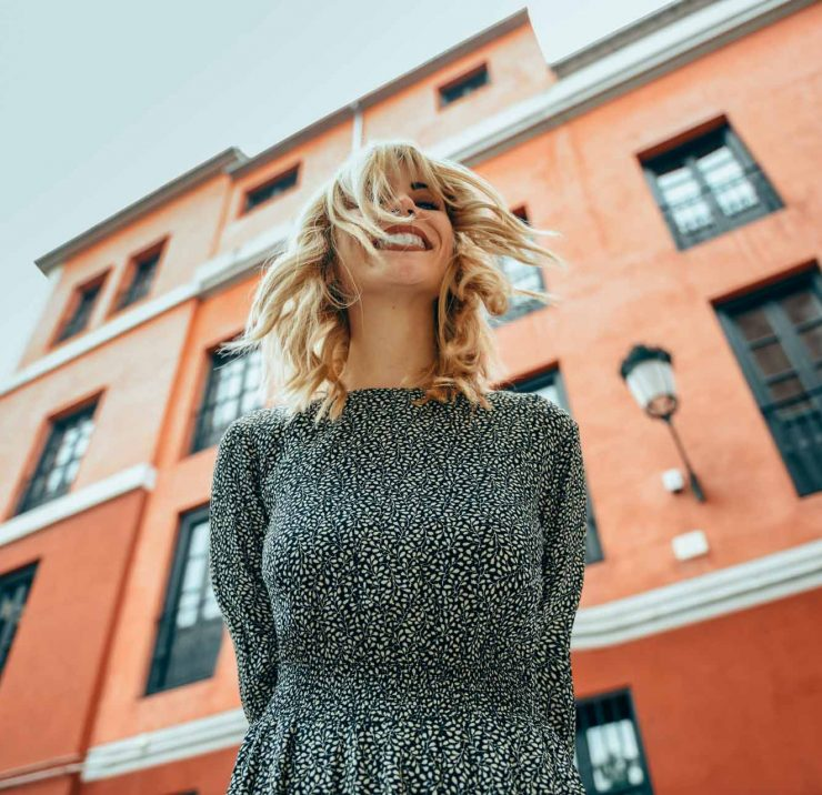 happy-young-woman-with-moving-hair-in-urban-backgr-367L9QH