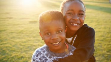 African elementary school boy and girl hugging outdoors