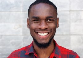 happy-young-african-man-smiling-against-gray-wall-PSC64N4