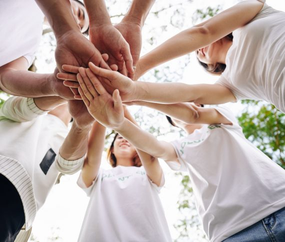 Team of student volunteers stacking hands to show support and unity before starting cleaning college campus