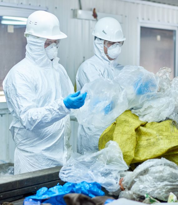 Portrait of two workers wearing biohazard suits at waste processing plant sorting recyclable plastic and cardboard on conveyor belt
