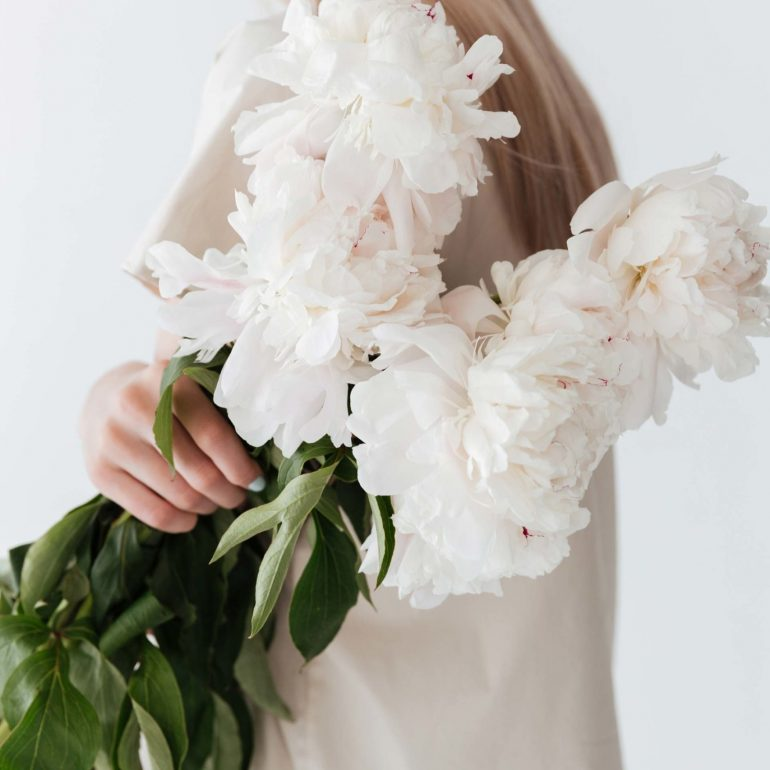 blonde-woman-standing-isolated-holding-flowers-P8B3XEP