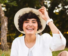 pretty-laughing-girl-sitting-in-hat-and-white-shir-9LAQS5W