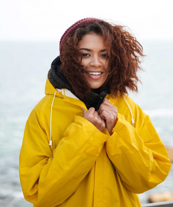 happy-african-curly-young-woman-wearing-yellow-PFCN4PV