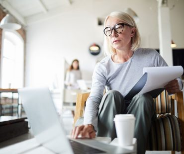 Mature businesswoman with document and laptop sitting on chair in office and browsing in the net
