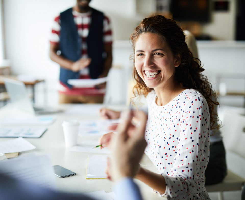 Happy young businesswoman sitting at desk and communicating with her colleagues during a meeting